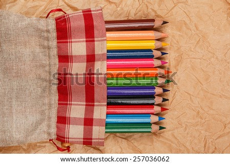 Multicolored pencils  over crumpled paper surface