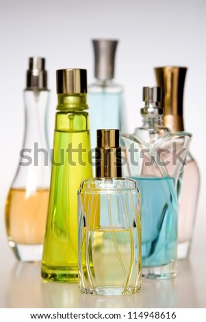 Multicolored perfumes in bottles of different shapes - stock photo