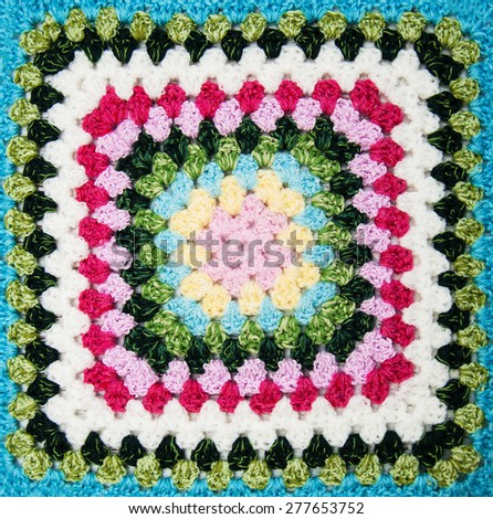 multicolored plaid square of crocheted - close up - stock photo