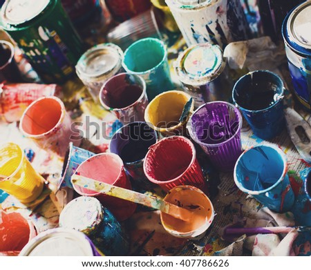Multicolored plastic cans with paints. Artist workplace background. Old dirty Paints background. Colorful artist palette. Soft toned. Creativity, visual art concept. Art and craft. Closeup - stock photo