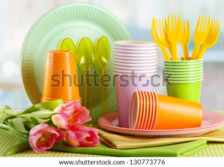 Multicolored plastic tableware on table with tulips close up - stock photo