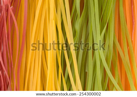 Multicolored raw long italian noodles - stock photo