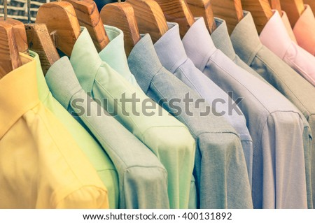 Multicolored shirts hanging on shop rack at weekly flea market - Elegant wardrobe sale concept and alternative retro colors fashion styling - Soft vintage filtered look - Shallow depth of field - stock photo