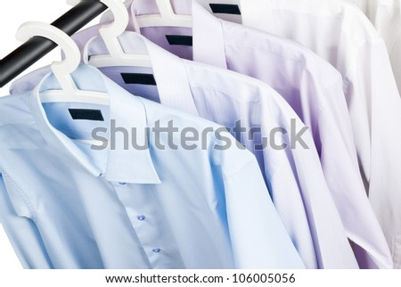 Multicolored shirts on plastic hangers, white background - stock photo