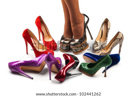 Multicolored shoes  and legs on a  white background - stock photo