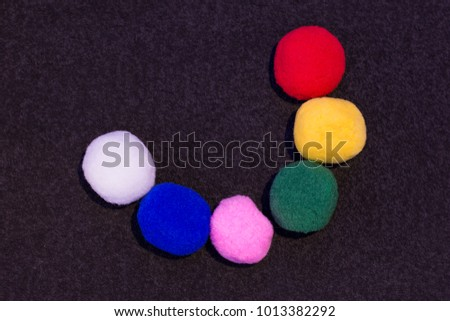 Multicolored soft holiday balls in the shape of a smile on a dark background