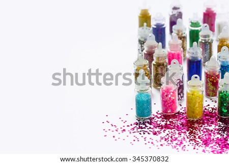 Multicolored sparkles for manicure and make-up in transparent bottles on a white background, place for text and selective focus - stock photo