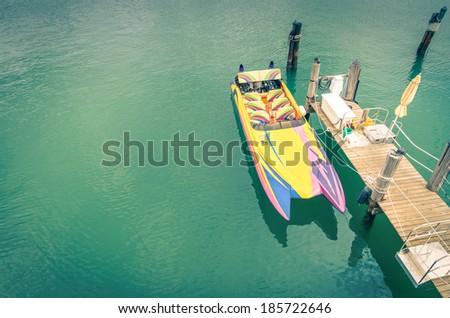 Multicolored speedboat ready to sail at wooden pier - Retro nostalgic image - stock photo