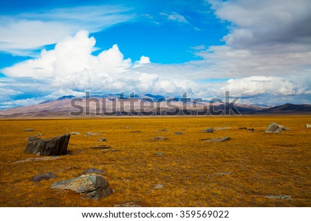 Multicolored steppe landscape with large stone in the foreground, mountains view, blue sky with clouds. Chuya Steppe, Kuray steppe in the Siberian Altai Mountains, Russia - stock photo
