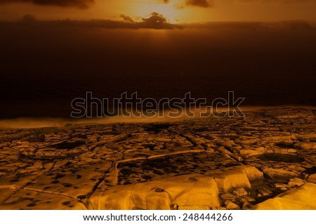 Multicolored sunset with amazing dramatic sky background and orange rock in foreground, amazing sunset, dramatic sunset with orange golden coast line background in Malta, Sliema - stock photo