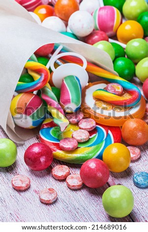 multicolored sweets and chewing gum in paper bags. Focus on the front round chewing gum - stock photo