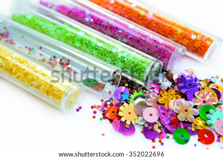 Multicolored tubes with sparkles scattered on a light background. The set for needlework. - stock photo