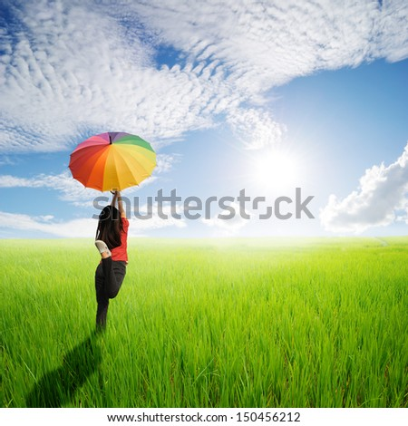 Multicolored umbrella woman jumping in green rice field and sun sky