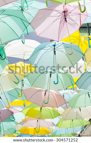 Multicolored umbrellas, sun umbrellas hanging colorful variety of the same size. - stock photo