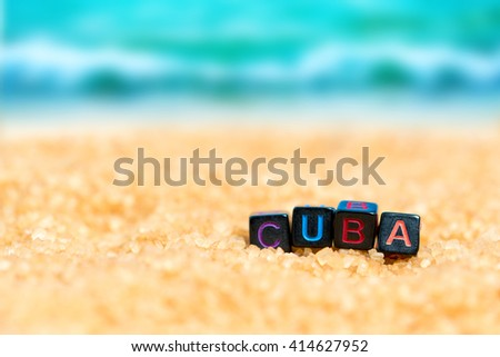 Multicolored word CUBA from black cubes in the sand on the background of beach and sea