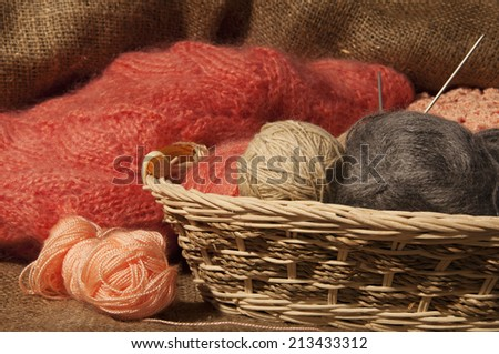 Multicolored yarn balls in a straw basket on the sacking - stock photo