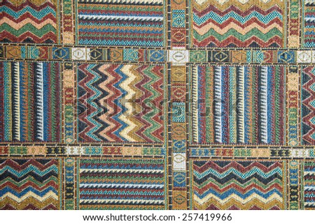 Multicoloured carpet with abstract ethnic ornaments, can be used as background - stock photo