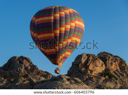 Multicoloured hot-air balloon over rocks. Clear blue sky in background.