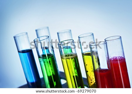 Multicoloured test tubes in the stand on blue background - stock photo