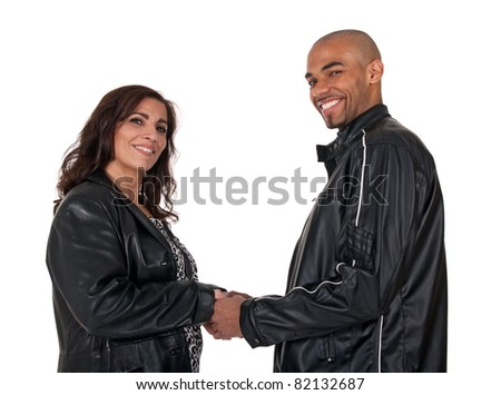Multicultural couple holding hands and smiling. Mature woman with younger man. - stock photo