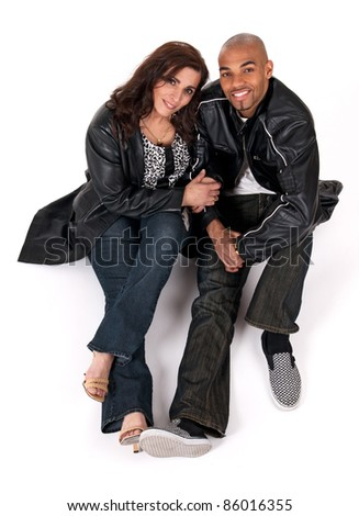 Multicultural couple. Mature woman holding the arm of her younger boyfriend. - stock photo