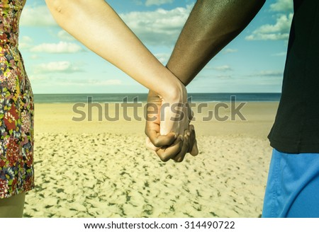 Multicultural  young  couple  hands holding  at beach sun sand and blue sky unity Instagram