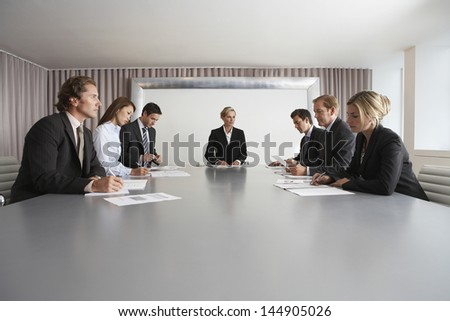 Multiethnic business people with paperwork in meeting room - stock photo