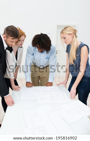 Multiethnic business team in a meeting standing around a table in the office discussing paperwork and brainstorming ideas - stock photo