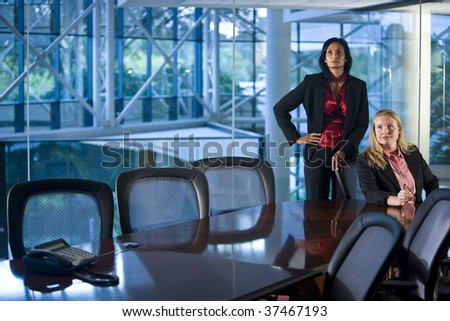 Multiethnic businesswomen in sitting at a boardroom table - stock photo