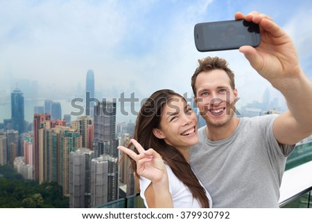 Multiethnic Chinese Caucasian couple in Hong Kong. Young people taking a smartphone selfie picture at viewpoint of famous attraction Victoria Peak, HK, China. Young multiracial group of people. - stock photo