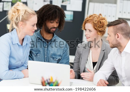 Multiethnic diverse young business team sitting having a serious discussion as they discuss information on a laptop computer - stock photo