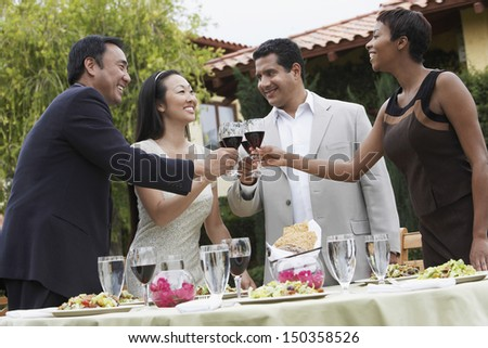 Multiethnic friends toasting wine in garden during dinner party