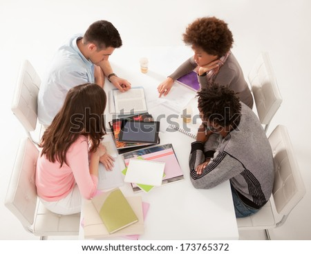 Multiethnic group of college students studying together in a workshop. - stock photo