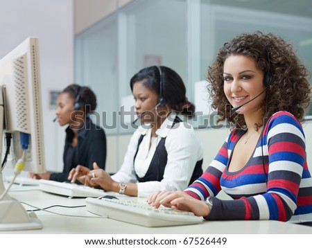 multiethnic group of female customer service representatives talking on the phone, with woman looking at camera. Horizontal shape, side view - stock photo