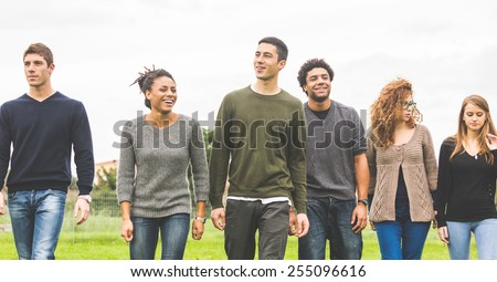 Multiethnic group of friends at park walking and enjoying time all together. Mixed race group with caucasian, black and asian people. Friendship, lifestyle, immigration concepts. - stock photo