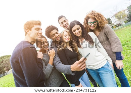 Multiethnic Group of Friends Looking at Mobile Phone - stock photo