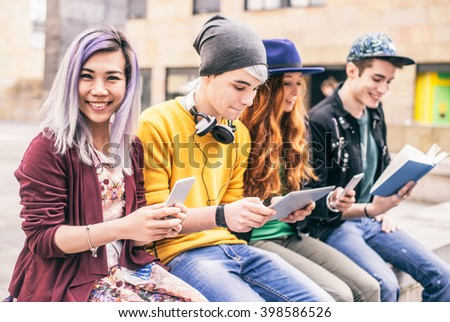 Multiethnic group of friends looking down at phone and tablet, concepts about technology addiction and youth - stock photo