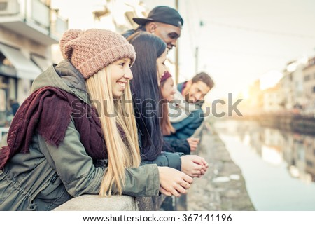 Multiethnic group of friends talking and having fun outdoors - Several students hanging out and city ant sunset in the background - stock photo
