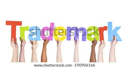 Multiethnic Group of Hands Holding Trademark - stock photo
