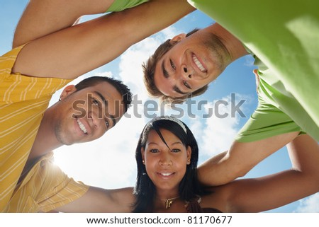 multiethnic group of male and female friends hugging and looking at camera with sky in background. Low angle view - stock photo