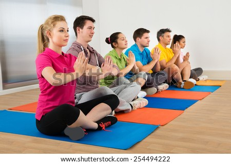 Multiethnic Group Of People Doing Meditation At Gym - stock photo