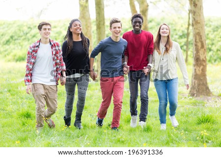 Multiethnic Group of Teenagers Walking at Park - stock photo