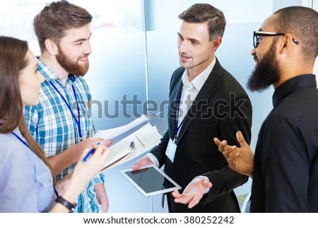 Multiethnic group of young business people standing and talking with chief executive in office - stock photo