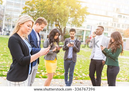 Multiethnic group of young people outdoor looking at their own smart phones. They are six persons, three men and three women, all wearing smart casual clothing. Technology and social media addiction. - stock photo