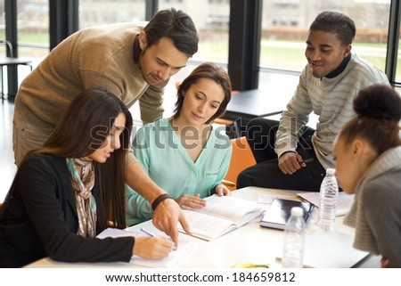 Multiethnic group of young students doing their studies together at a table. Mixed race people in cooperation with their school assignment.