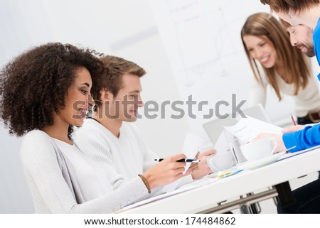 Multiethnic happy business team sitting at a table in a meeting planning their business strategy - stock photo