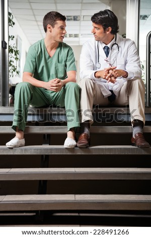 Multiethnic medical colleagues having discussion while sitting on steps - stock photo