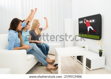 Multiethnic Women Sitting On Couch Cheering Watching Rugby Match - stock photo