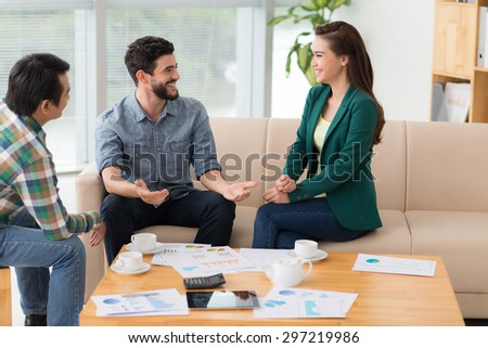Multiethnic young colleagues laughing and talking in the office - stock photo
