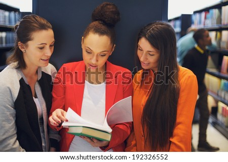 Multiethnic young students reading a book in library. Standing in public library sharing reference book for their studies. - stock photo